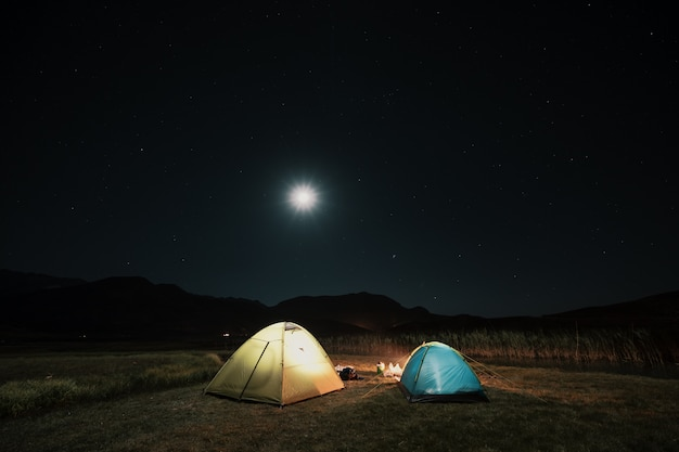 Tourist tents in camp among meadow in the night mountains