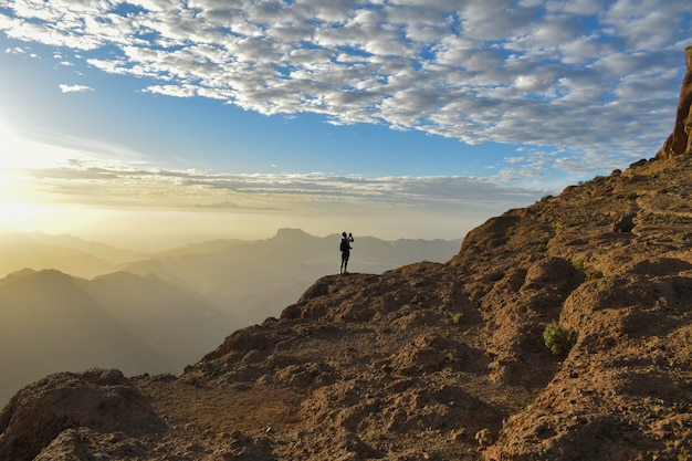 Turista sulla cima di una montagna rocciosa a gran canaria, spain