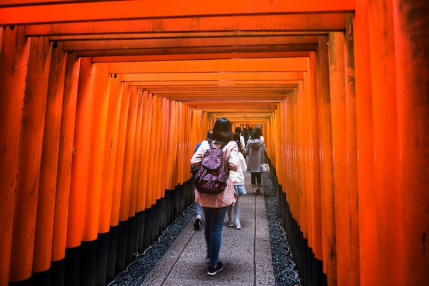 Tourist at torii gate, fushimi inari, kyoto