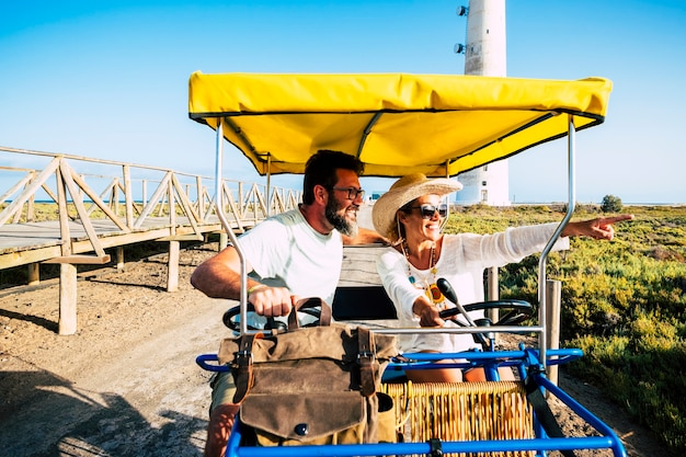 Tourist and tourism people concept with cheerful and happy adult couple on a surrey bike enjoying the outdoor leisure activity on vacation summer holiday season together
