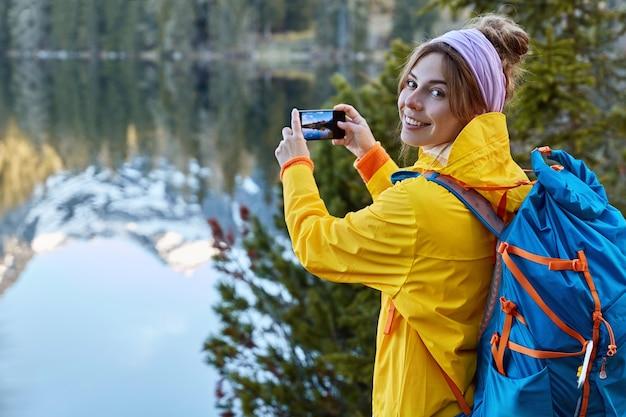 관광 여행자는 손에 스마트 폰을 들고 여행 중 파노라마 풍경 사진을 만들고 산에서의 여행을 존경하며 호수 근처에서 포즈를 취합니다.