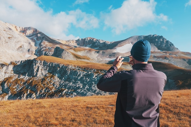 Tourist traveler photographs mountains covered with clouds on a smartphone