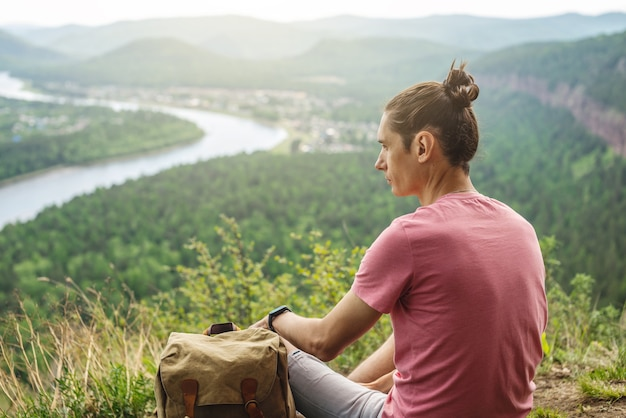A tourist traveler with a backpack is sitting on the edge of a cliff and is looking on a green forest valley with the river