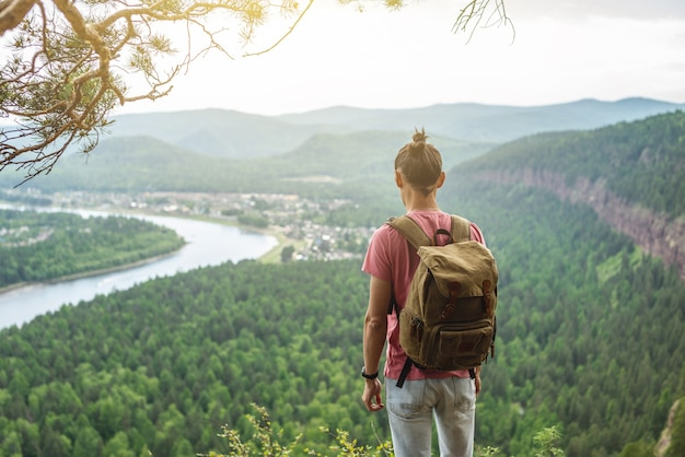 A tourist traveler with a backpack is standing on the edge of a cliff and is looking on a green valley with the river