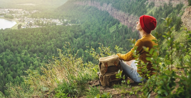 A tourist traveler with a backpack and a red hat is sitting on the edge of a cliff and is looking on a green forest valley with the river