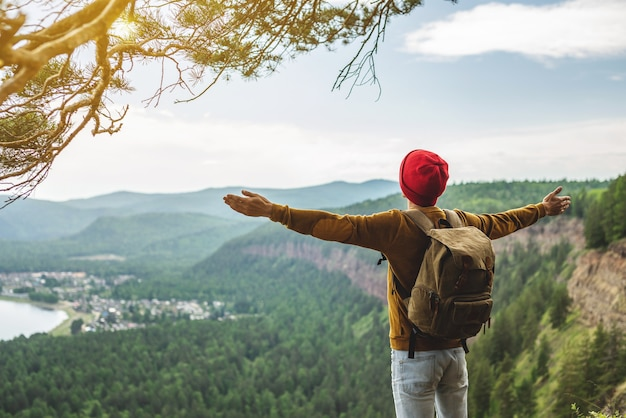 A tourist traveler with a backpack and a red hat is standing on the edge of a cliff in front of a green valley with his arms spread wide
