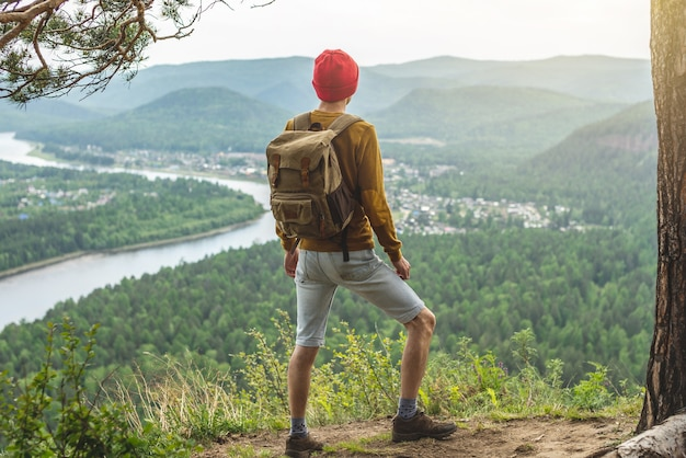 A tourist traveler with a backpack and a red hat is standing on the edge of a cliff and is looking on a green valley with the river