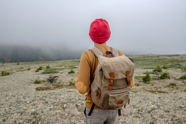 A tourist traveler with a backpack and a red hat is standing in the mountains and looking at the thick fog ahead