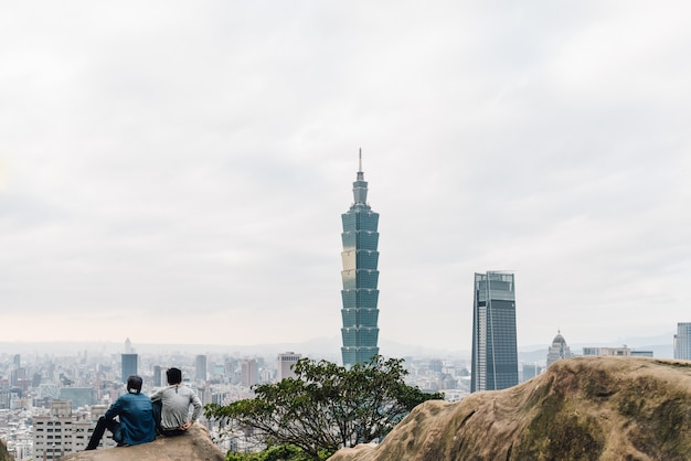 Tourist trekkers sitting on stones and seeing taipei 101 skyscraper from xiangshan elephant mountain in the evening in taipei, taiwan.