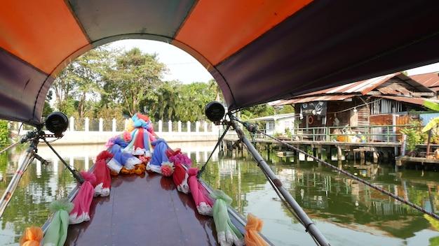 Туристическая поездка по азиатскому каналу. вид на спокойный канал и жилые дома с украшенной традиционной тайской лодки во время туристической поездки в бангкок.