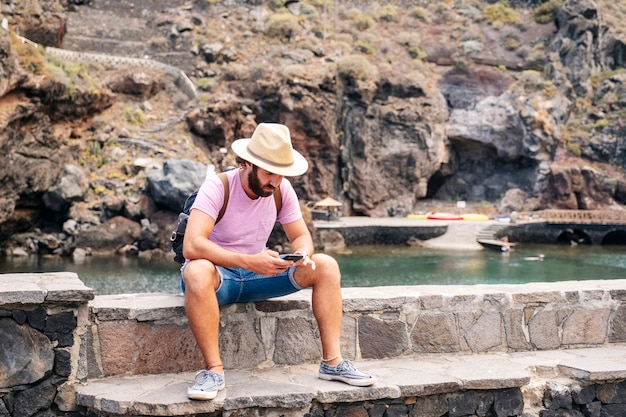 A tourist uses a mobile phone in a coastal town el hierro, canary islands