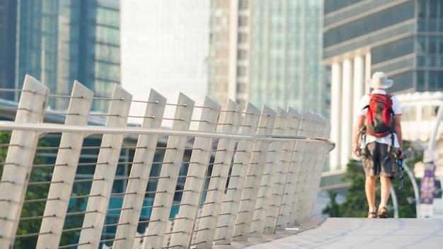 Tourist walk in city pedestrian bridge with exterior modern building.