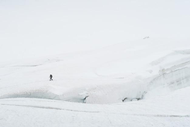 Tourist walking on the glacier near the crack. view to the mensu glacier, russia.