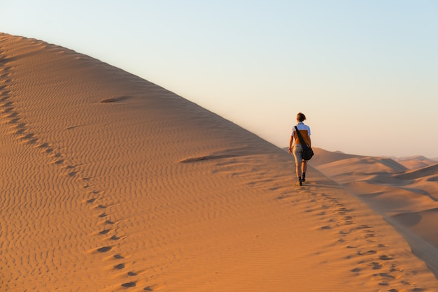 Tourist walking on scenic dunes in the namib desert, namibia