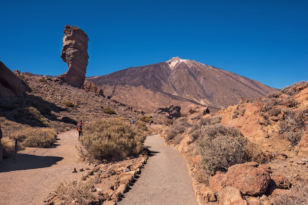 Tourist walking in teide national park on a sunny day tenerife, canary islands, spain