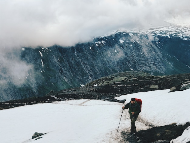Tourist walks across the snow in the mountains