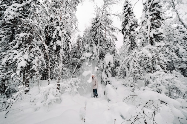 A tourist walks in a snow-covered forest. winter forest in estonia.journey through the winter forest