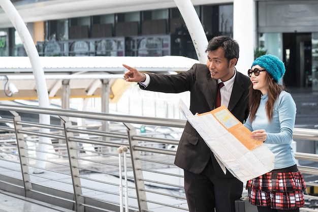 Tourist watch map searching direction sightseeing and ask for place location on mobile phone tablet.