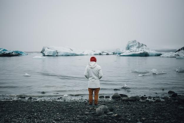 Турист наблюдает за ледником в воде в исландии