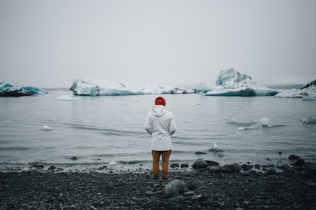 Tourist watches glacier in water in iceland