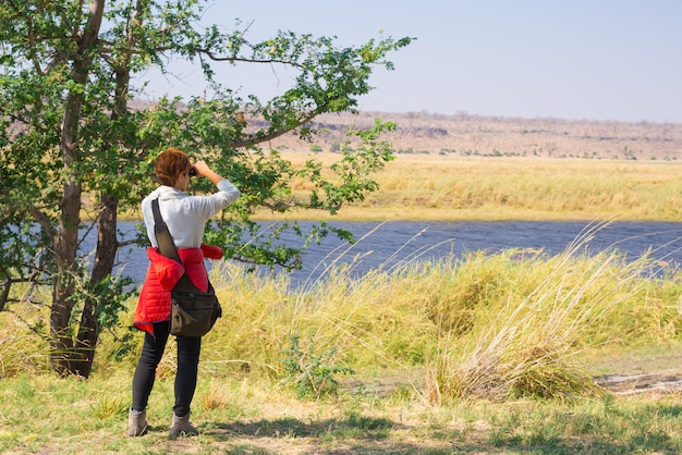Tourist watching wildlife by binocular on chobe river, namibia botswana border, africa. chobe national park, famous wildlilfe reserve and upscale travel destination.