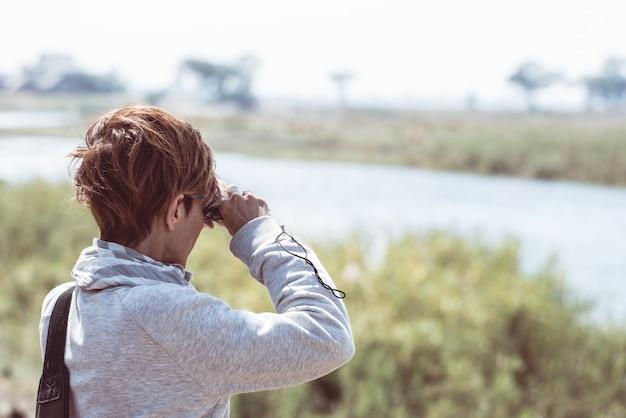 Tourist watching wildlife by binocular on chobe river, namibia botswana border, africa.