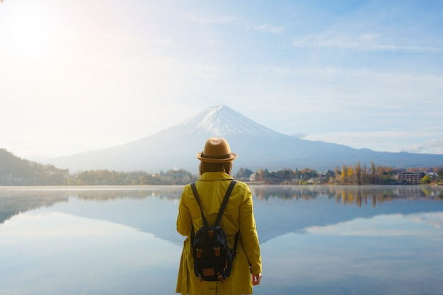Турист в желтой куртке и шляпе смотрит на гору фудзи на озере кавагутико, япония
