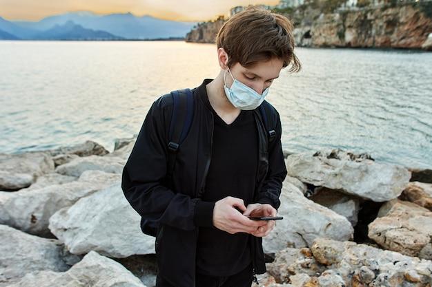 마스크를 착용 한 관광객은 코로나 바이러스 전염병으로 인한 통금 시간 동안 안탈리아의 바다 근처를 산책합니다.