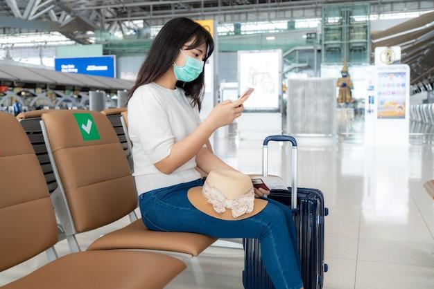 항공사 비행 상태를 검색하는 휴대 전화를 사용하여 마스크를 착용하는 관광객