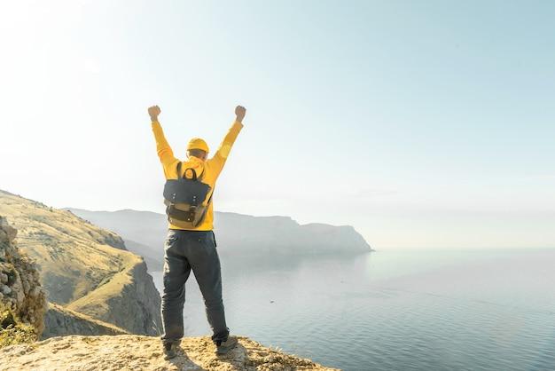 배낭을 메고 있는 한 남자가 유쾌하게 손을 들고 해질녘 바다의 아름다운 전망을 즐깁니다.