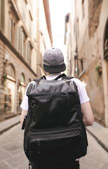 大きな黒いバックパックを持った観光客が街の狭い通りにいて、楽しみにしています。