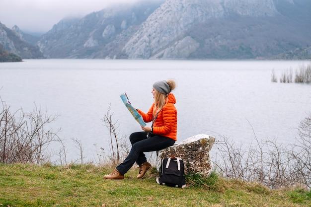 湖の隣の自然の中で座っている地図を持っている観光客は、ウールの帽子とオレンジ色のコートを着ています
