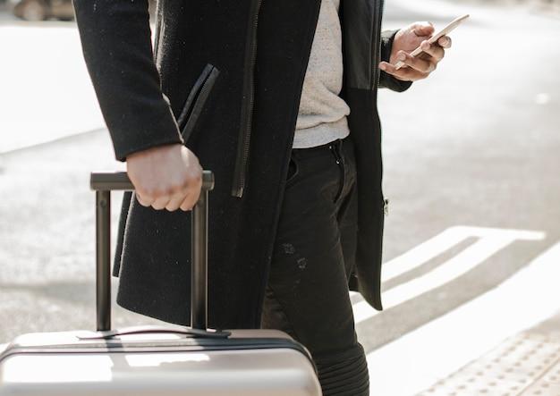 휴대전화를 보고 있는 여행가방을 든 관광객