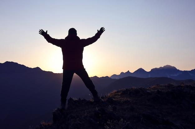 팔을 가진 관광은 새벽에 산에 서 제기