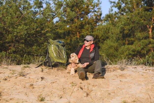 배낭과 개가있는 관광객은 숲에서 휴식을 취합니다.