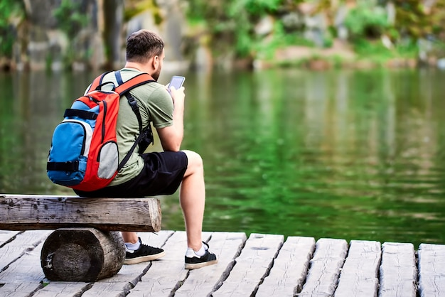 A tourist with a backpack on his back sits on a tree bench by the lake and looks at the phone