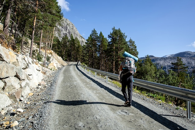 Tourist with a backpack is walking along a gravel road