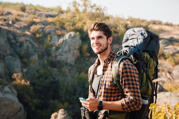 Турист с рюкзаком, глядя в горы