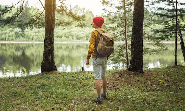 A tourist with a backpack and a red hat is walking in the forest among the trees
