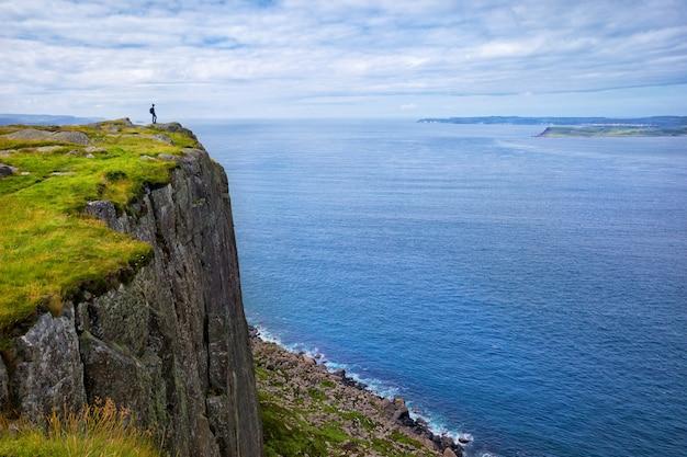 Турист с рюкзаком стоит на скале fair head, северная ирландия, великобритания