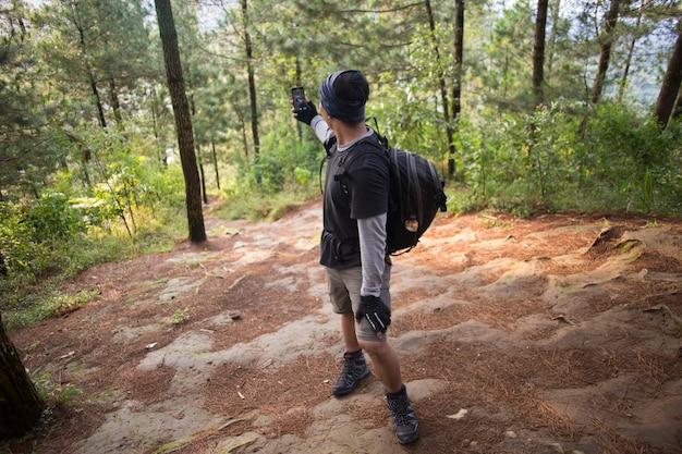 Турист с рюкзаком фотографирует с помощью смартфона в горах