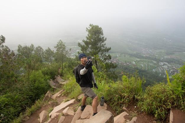 バックパックを持った観光客が山でスマートフォンで写真を撮る
