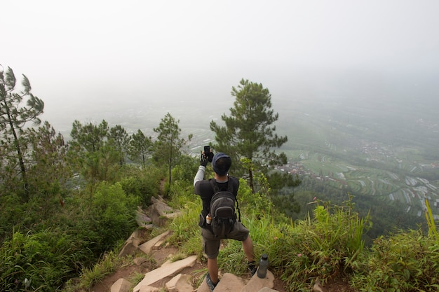 Tourist with backpack takes photos with smart phone in the mountains