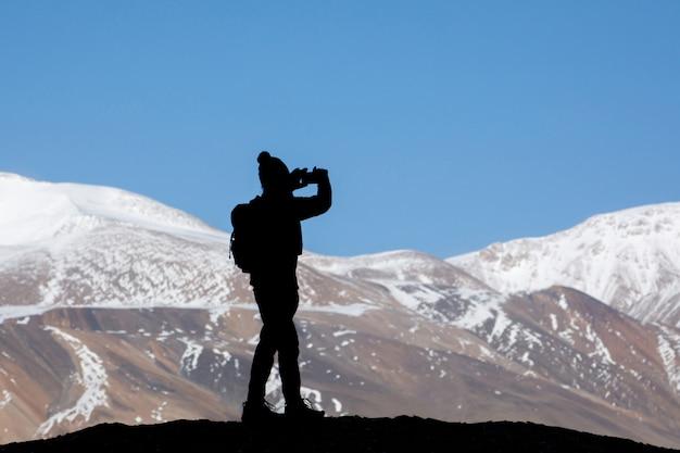 Турист с рюкзаком фотографирует на скале в красивых горах вид на снежное озеро цо морири в лех ладакх индия