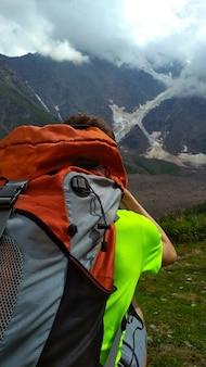 배낭을 메고 산 사진을 찍는 관광객