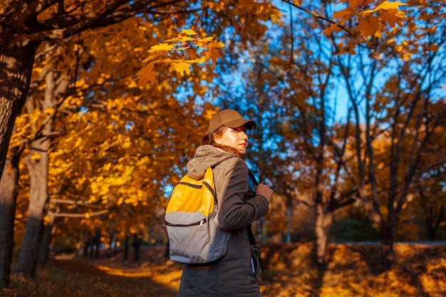 Tourist with backpack walking in autumn forest. young woman travel at sunset