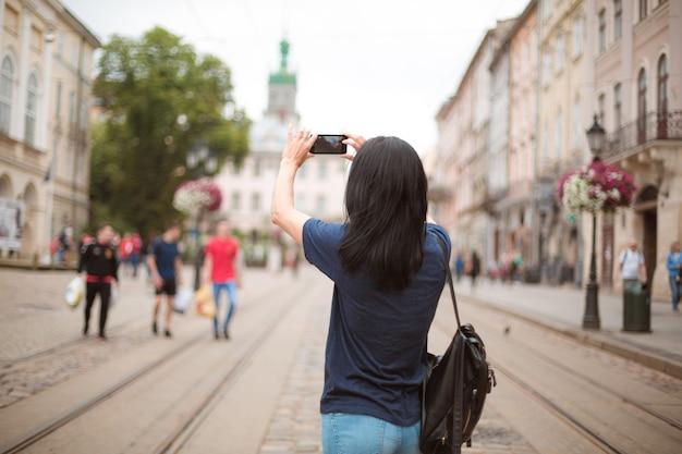 배낭을 메고 도심을 걷고 스마트폰으로 사진을 찍는 관광객. 텍스트를 위한 공간