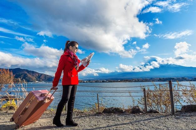 Turista con bagaglio e mappa al monte fuji, kawaguchiko in giappone.