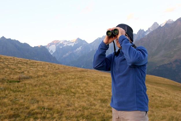 조지아의 산악 지역에서 쌍안경으로 보는 관광객