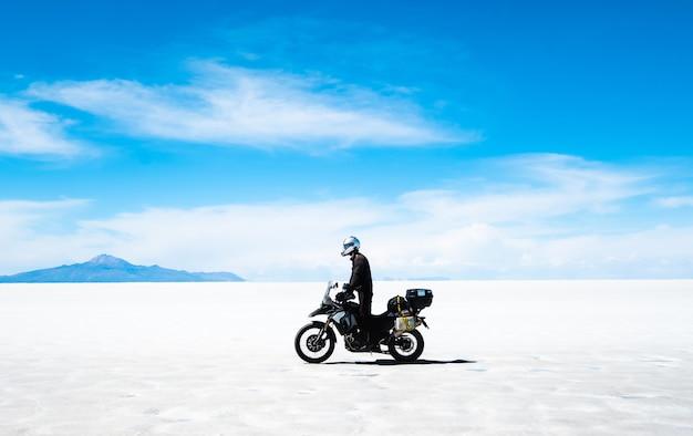 햇빛 살라르 데 우유니에서 오토바이를 타고 장비를 가진 관광객